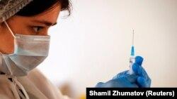 Медработник держит в руках шприц с вакциной. Иллюстративное фото.