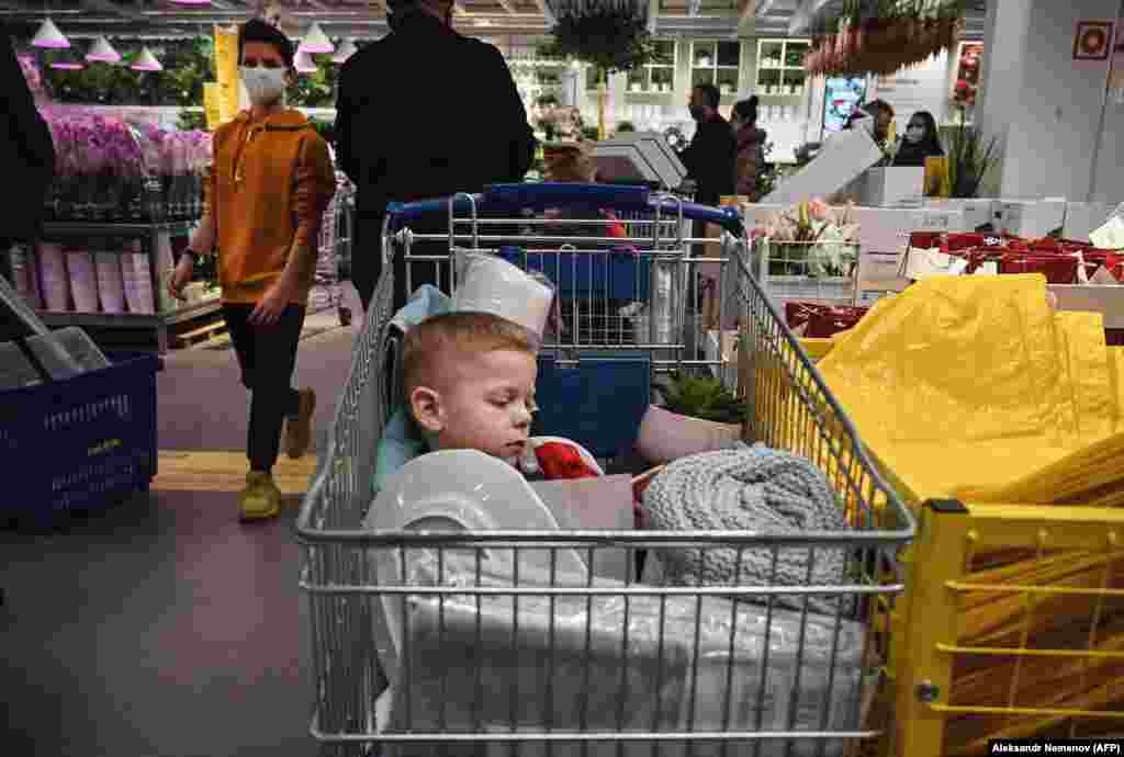 A boy sleeps in a shopping trolley while his parents shop at a store in Moscow. (AFP/Aleksandr Nemenov)
