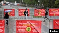 Прохожие возле ограждений с баннерами на тему коронавируса. Алматы, 23 мая 2021 года
