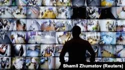 Az orosz Központi Választási Bizottság moszkvai központjában figyeli egy férfi a szavazóhelyiségbe kihelyezett kamerákat 2021. szeptember 19-én