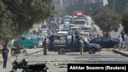 A police vehicle is parked on a road covered with stones thrown by protesters in Karachi on January 7, the fifth day that demonstrations against the killing of 11 Shi'ite Hazara coal miners brought cancellations and delays to roads, railways, and airlines.