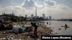 """Angelita Imperio, """"a folyó egyik harcosa"""" gyűjti zsákba a szemetet Manilában a Pasig folyó partján."""