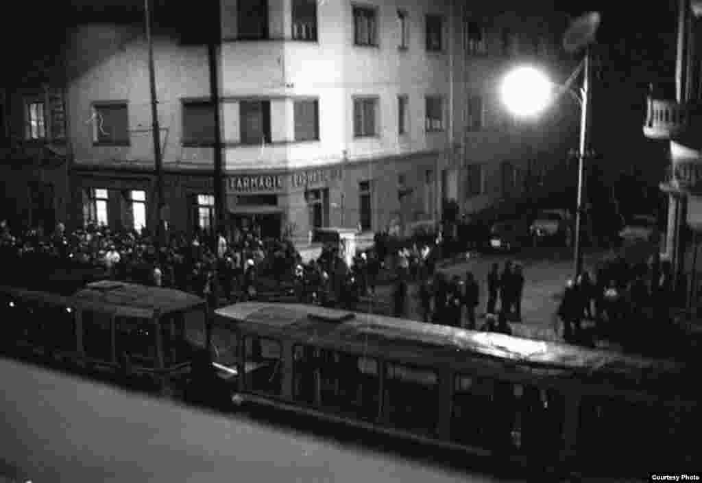 """Timișoara, 16 decembrie 1989. Tramvaie oprite de manifestanți curajoși în apropiere de Piața Maria, în fața Bisericii Reformate în care se afla Lazlo Tokes. Ei încercau în acest fel să anunțe orașul - prin blocajul creat - că în zonă """"se întâmplă ceva!"""""""