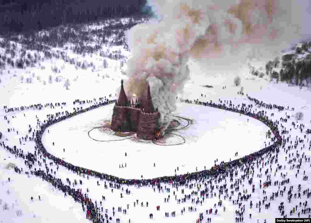 People watch a castle-shape wooden construction called Corona Tower -- created by Russian artist Nikolai Polissky -- burn as part of celebrations in the village of Nikola-Lenivets, about 200 kilometers southwest of Moscow.