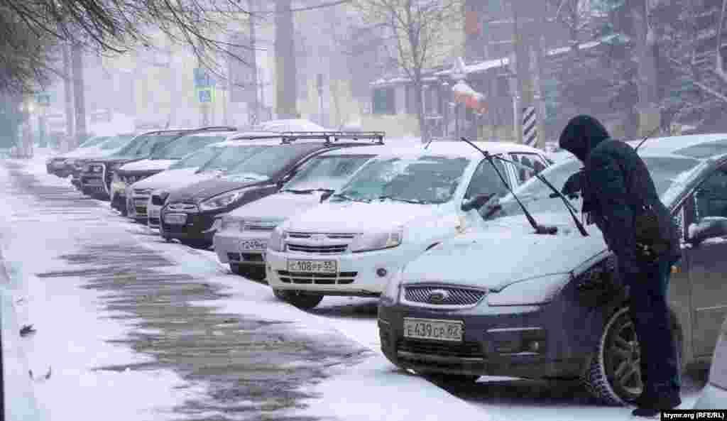 Чоловік очищає від снігу свій автомобіль на стоянці біля будівлі парламенту Криму
