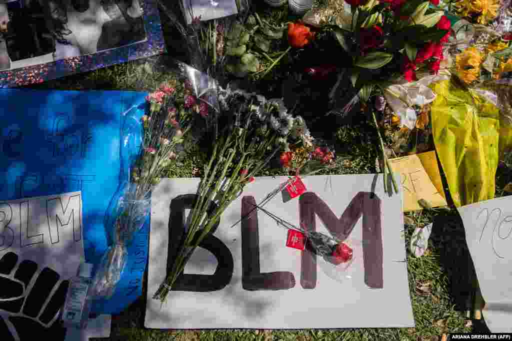 """A """"BLM"""" Black Lives Matter sign and flowers can be seen on the ground at a makeshift memorial at Palmdale City Hall for Robert Fuller, a young black man who was found hanging from a tree, on June 16, 2020, in Palmdale, California."""