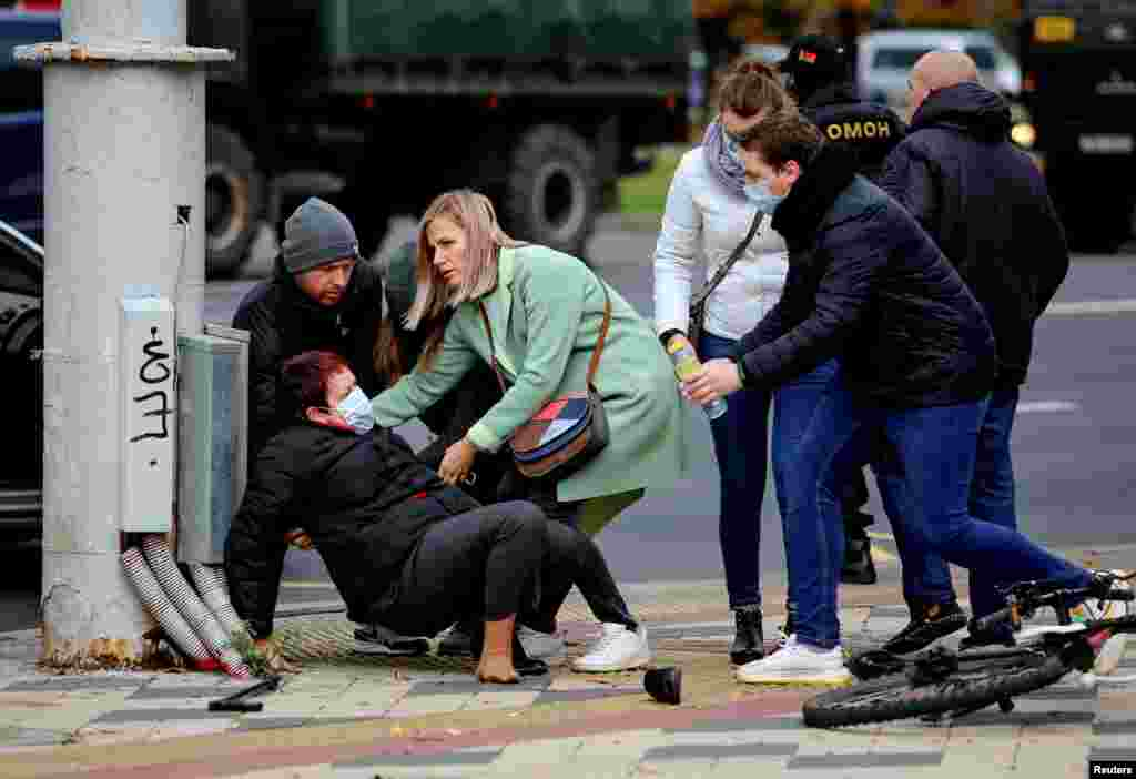 People assist a woman after she collided with a Belarusian law enforcement officer during a rally of opposition supporters to reject the presidential election results in Minsk on November 1. (Reuters)