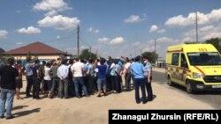 Вышедшие на протест жители Бестамака, сотрудники полиции и машина неотложки