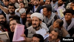 Afghans gather outside the passport office in Kabul on October 6 after Taliban officials announced they will start issuing passports to its citizens again.