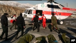 In this photo released by Iran's Red Crescent Society, rescuers work to unload bags containing bodies of mountaineers who died after avalanches in a mountainous area north of the capital, Tehran, on December 26.