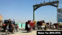Afghans flee their villages after the fighting intensified between Taliban militants and security forces in Lashkar Gah, the provincial capital of restive Helmand Province, on October 12.