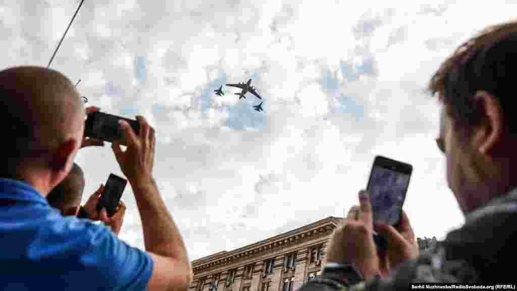 Глядачі фотографують проліт над Хрещатиком важкого військово-транспортного літака Іл-76 у супроводі багатоцільових винищувачів Су-27