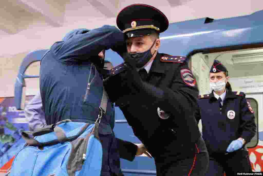 Wearing a protective face mask amid the coronavirus pandemic, a Russian police officer detains a man at a metro station in Novosibirsk on October 23. (TASS/Kirill Kukhman)