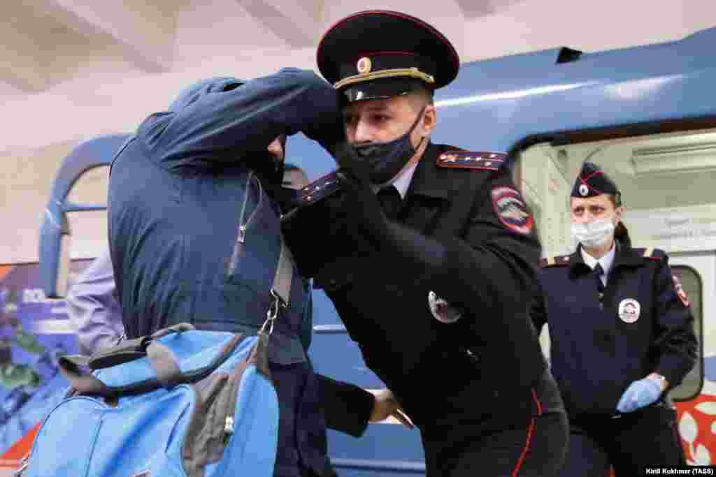 Një zyrtar policor rus teksa arreston një person në një stacion metroje në Novosibirsk më 23 tetor. (TASS/Kirill Kukhman)