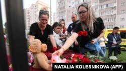 RUSSIA -- TATARSTAN -- A woman places a toy at a makeshift memorial for victims of the shooting at School No. 175 in Kazan on May 11, 2021.