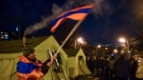 ARMENIA -- An opposition supporter waves an Armenian flag by tents set near the National Assembly building during a protest demanding the resignation of Prime Minister Nikol Pashinyan in Yerevan, February 25, 2021