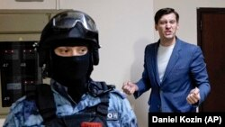 Russian opposition activist Dmitry Gudkov speaks to the media as police search his country home outside Moscow on June 1.