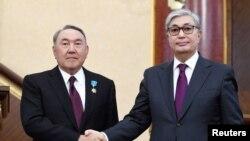 Касым-Жомарт Токаев, к которому только что перешли президентские полномочия (слева), с подавшим накануне в отставку Нурсултаном Назарбаевым в тогда еще Астане, 20 марта 2019 года.
