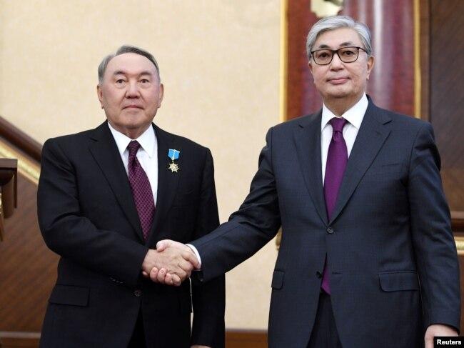 Исполняющий обязанности президента Казахстана Касым-Жомарт Токаев (справа) пожимает руку своему предшественнику Нурсултану Назарбаеву во время совместного заседания палат парламента в Астане, Казахстан, 20 марта 2019 года.