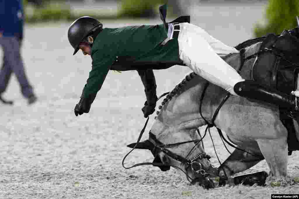 Ireland's Shane Sweetnam falls from his horse Alejandro while competing competing during the equestrian jumping team qualifying at Equestrian Park in Tokyo at the 2020 Summer Olympics, Friday, Aug. 6, 2021, in Tokyo, Japan.