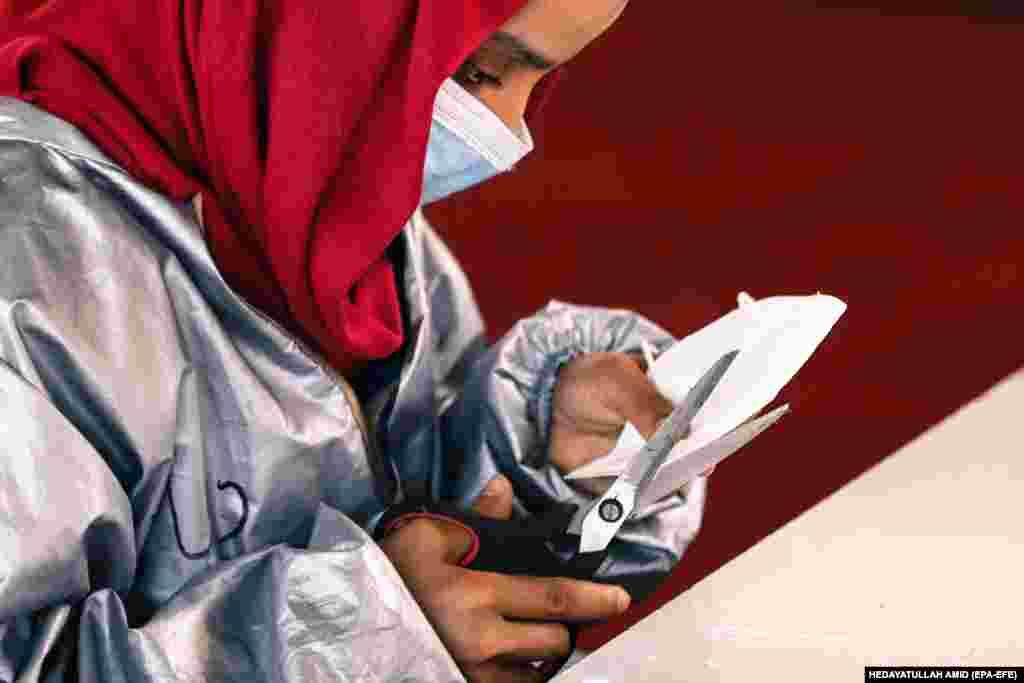 An Afghan woman produces protective face masks at a factory in Kabul. (epa-EFE/Hedayatullah Amid)
