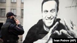 Петербургда Навальнийга бағишланиб чизилган граффити қаршисида турган полициячи
