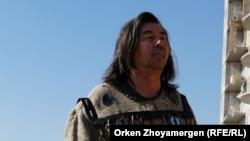 Суретші Асхат Ахмедияров Талдыкөлге топырақ төгіп жатқан жүк көліктерінің алдында. Нұр-Сұлтан, 7 қыркүйек, 2021 жыл.