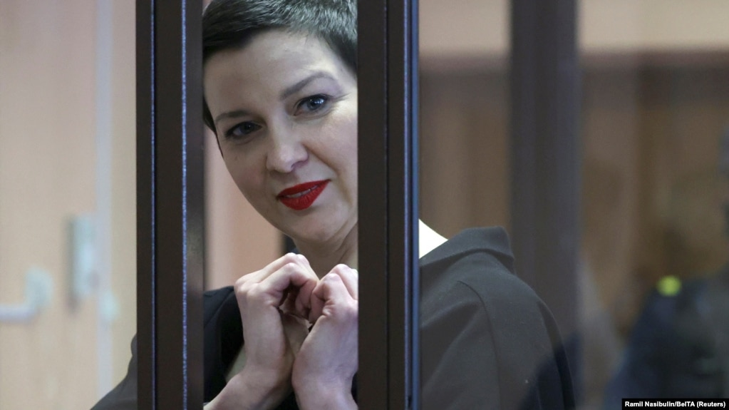 Maryya Kalesnikava forms a heart shape to supporters from inside a defendants' cage at her trial in Minsk on September 6.