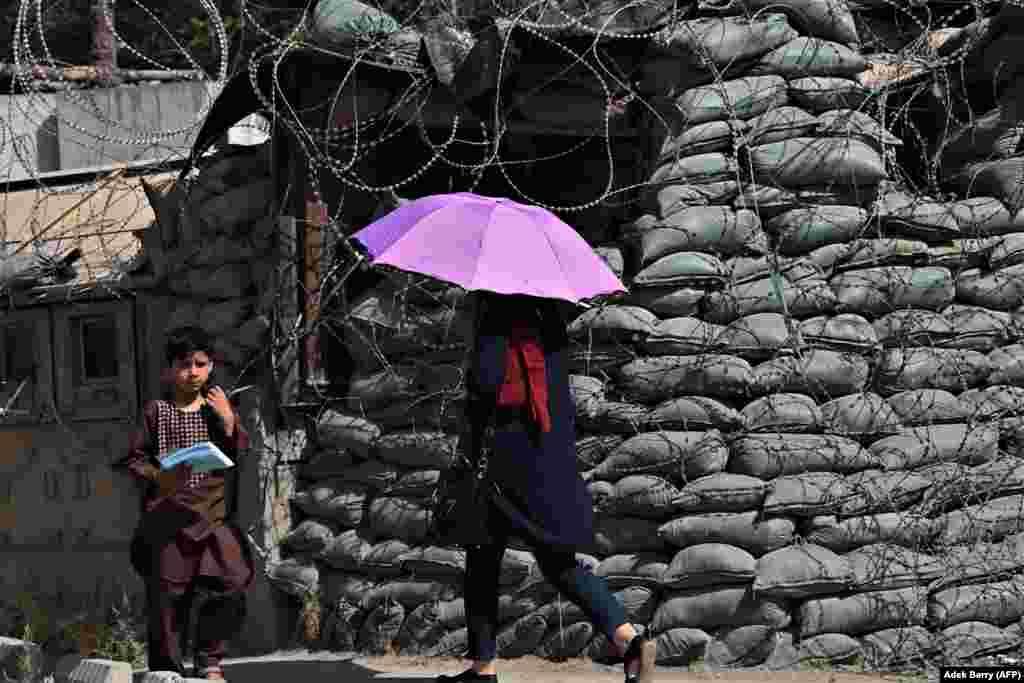 Люди проходят мимо обнесенного колючей проволокой поста безопасности в Кабуле, Афганистан