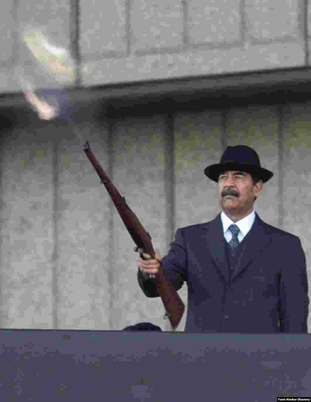 Президент Ирака Саддам Хусейн стреляет из винтовки, которую держит в одной руке. В другой — сигара. Действие происходит во время военного парада в декабре 2000 года.