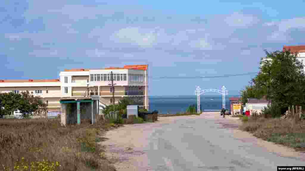 Улица Нововосточная ведет к главному входу с аркой на пляжи. Слева – автобусная остановка. В Феодосию рейсовые автобусы оттуда отправляются три раза в день и один раз в неделю, во вторник, в райцентр Ленино
