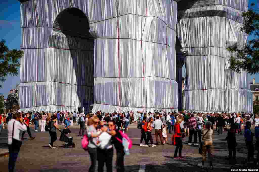 """După ce a fugit de regimul comunist din Bulgaria, Christo a promis să nu va renunța la """"niciun milimetru"""" din libertatea sa și că nu va permite ca arta lui să fie distrusă. Niciunul dintre proiectele masive realizate de el și Jeanne-Claude nu au fost finanțate din bani publici. În fotografie, vizitatori se adună pentru a asista la vernisarea instalației artistice """"Arcul de Triumf Înfășurat""""."""