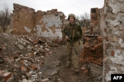 A Ukrainian soldier patrols near the front line with Russia-backed separatists near the city of Marinka in the eastern Donetsk region on April 12.