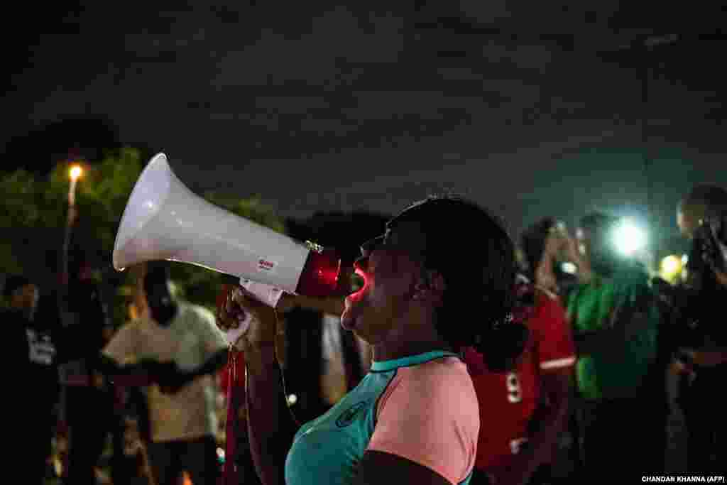 Eva Snow (Center),42, shouts slogans and speak to the protestors outside a burned Wendy's restaurant on the third day following Rayshard Brooks shooting death by police in the restaurant parking lot in Atlanta, Georgia, June 15, 2020.
