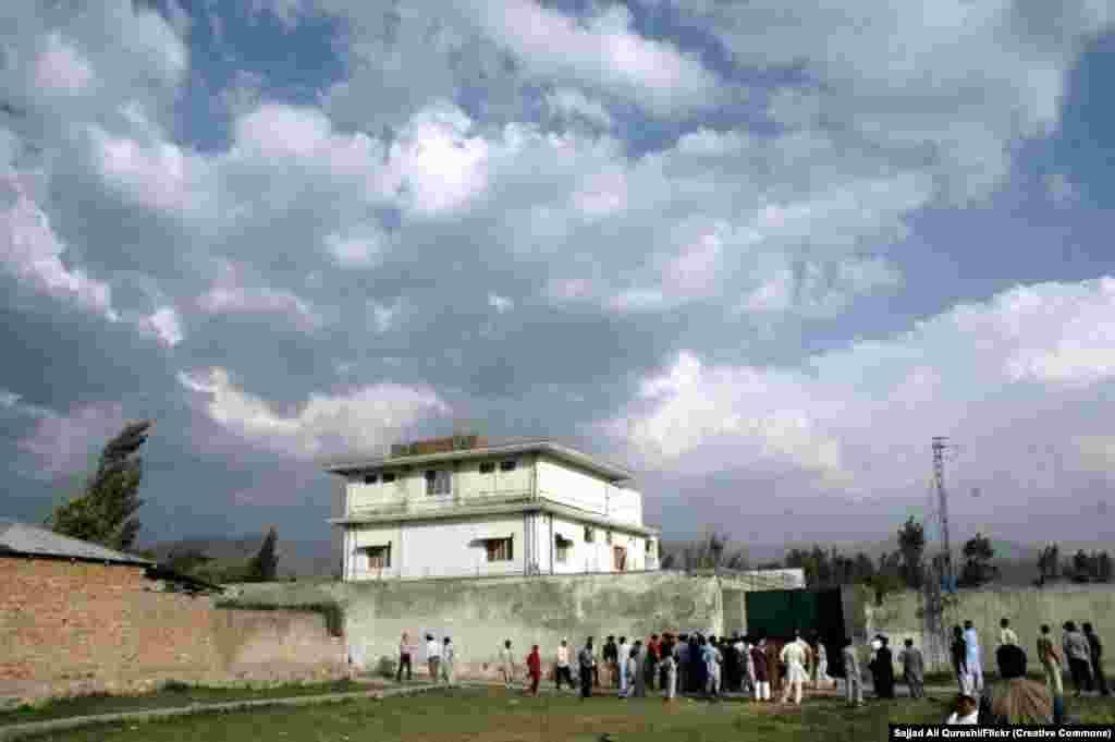 Местные жители собираются вокруг резиденции бин Ладена 4 мая 2011 года. Расположение комплекса в нескольких минутах ходьбы от пакистанской военной базы вызвало подозрение, что военные знали о местонахождении террориста