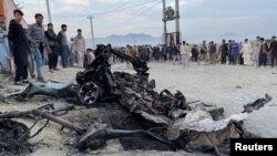 People stand at the site of a deadly bomb blast in Kabul on May 8.