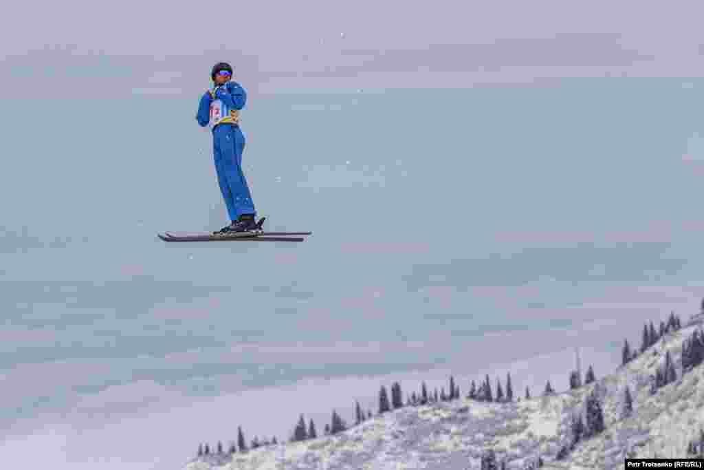 Фристайлдан әлем чемпионатына қатысушы жаттығу орындап жатқан сәт. Алыстан мұнартқан бұлттың астында Алматы қаласы жатыр.