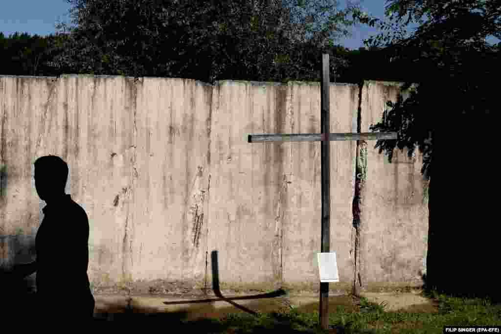 A cross stands next to a remaining section of the Berlin Wall at the memorial site near Griebnitzsee, pictured in Berlin