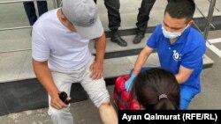 Медработник помогает активисту Ырысбеку Токтасыну, который получил ссадину в полицейском кольце. Алматы, 6 июля 2021 года