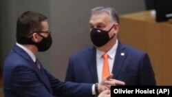 Польшанын премьери Матеуш Моравецки (солдо) Венгриянын өкмөт башчысы Виктор Орбан менен Евробиримдиктин саммити маалында баарлашууда. Брюссел. 2020-жылдын 10-декабры.