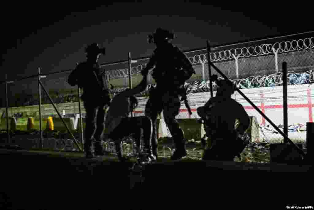 Брытанскія і канадзкія салдаты дапамагаюць афганцу перабрацца ў тую частку аэрапорту, якая кантралюецца міжнароднымі сіламі.