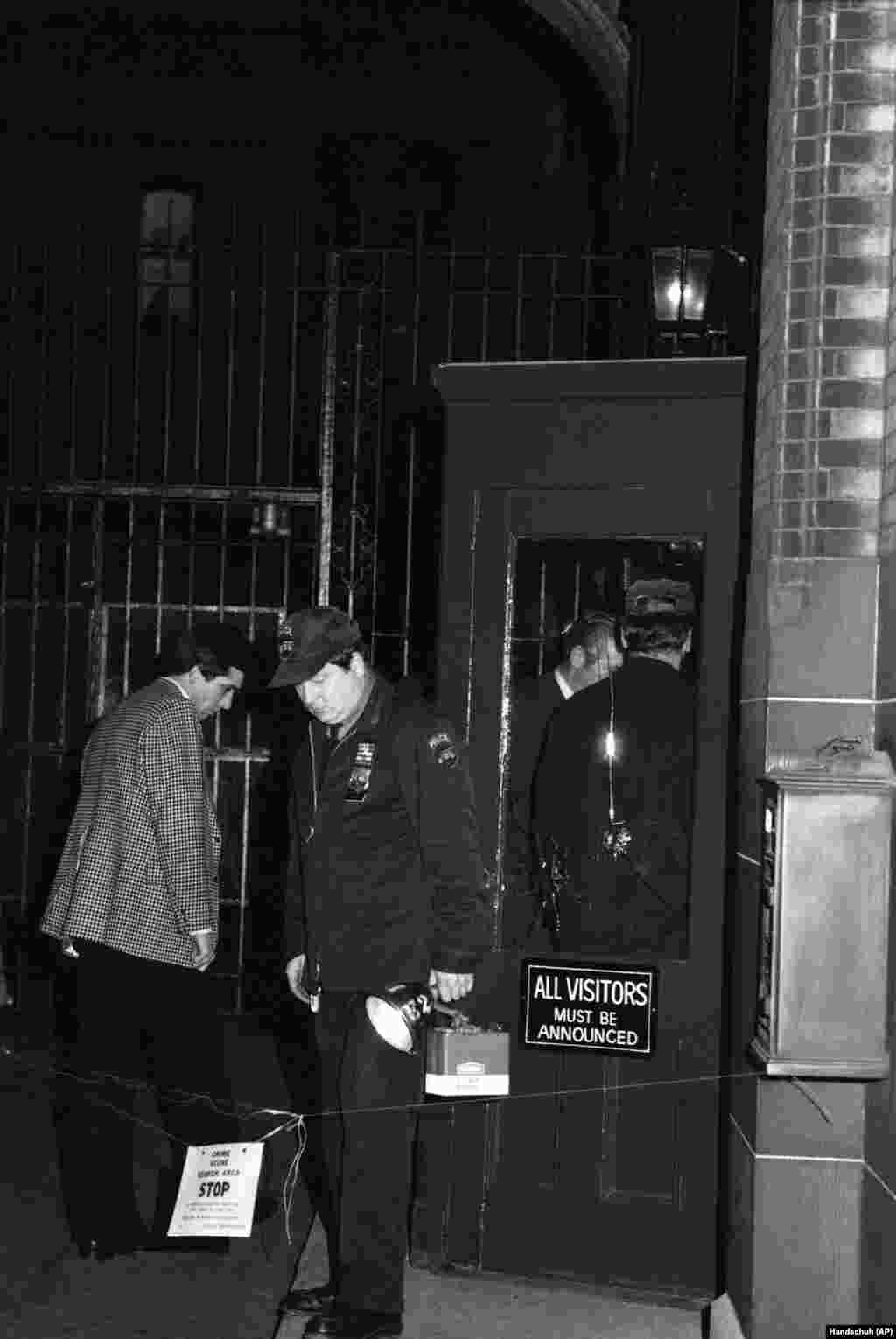 Police examine entrance alcove to the Dakota Apartment Building in New York, Monday, Dec. 8, 1980 after John Lennon was shot and killed as he returned home to the building.Bullet holes can be seen in the glass in the door.