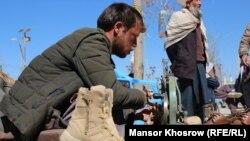 اسماعیل رضایی در کنار جاده خاکی شهر فیروزکوه مرکز ولایت غور کفاشی میکند