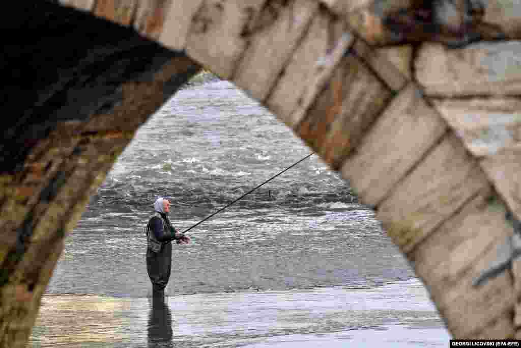 Рыбак ждет улова на берегу реки Вардар в Скопье, Северная Македония. (epa-EFE/Георги Ликовски)