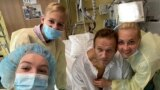 Russian opposition politician Aleksei Navalny and his family members pose for a picture at the Charite hospital in Berlin on September 15.