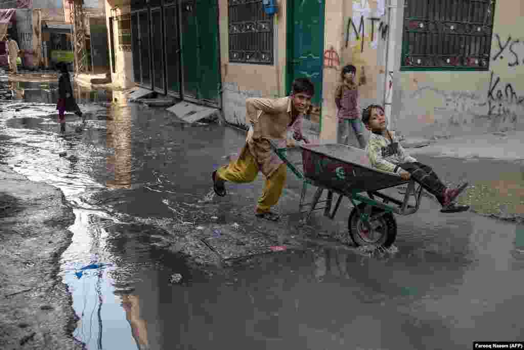 Children play in puddles of wastewater on a street in a slum area on the outskirts of Islamabad. (AFP/Farooq Naeem)