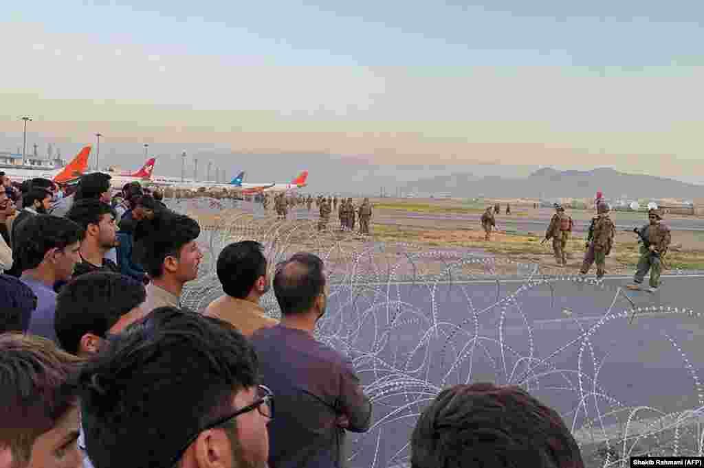 Натовп збирається в аеропорту, поки солдати США перебувають на варті