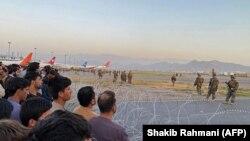 Afganii (stânga) se adună pe aeroport în vreme ce militarii americani fac de gardă, Kabul, 16 august 2021.