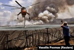Egy helikoptert töltenek fel vízzel Szpaszovuninál, Korinthosz közelében, Görögországban 2021. július 23-án