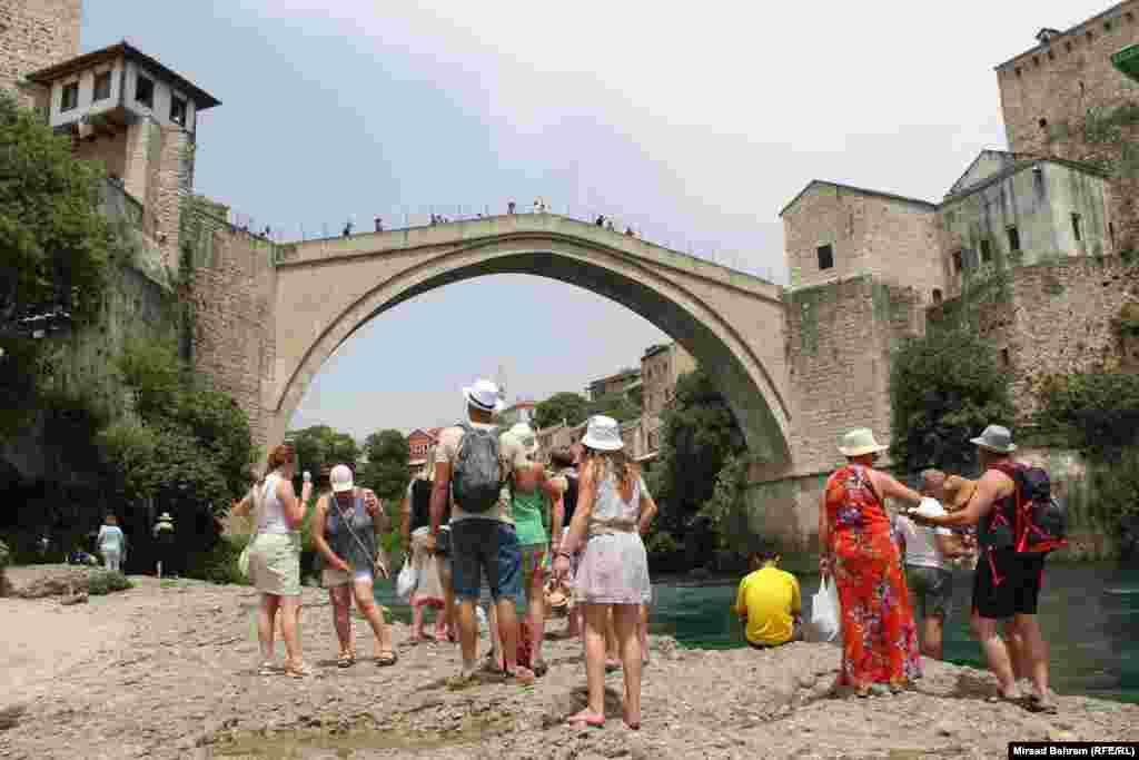 Grupa turista sa šeširima na glavama ispod Starog mosta u Mostaru.
